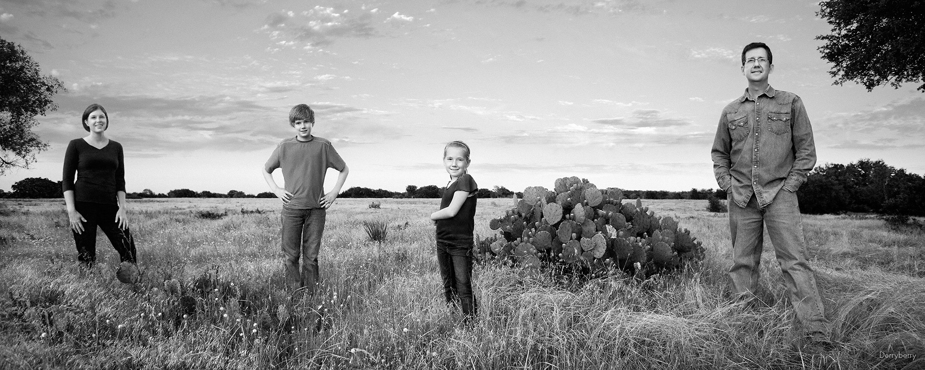 Black and white panoramic group portrait  of the Henderson family on their  ranch in West Texas by photographer John Derryberry Photography