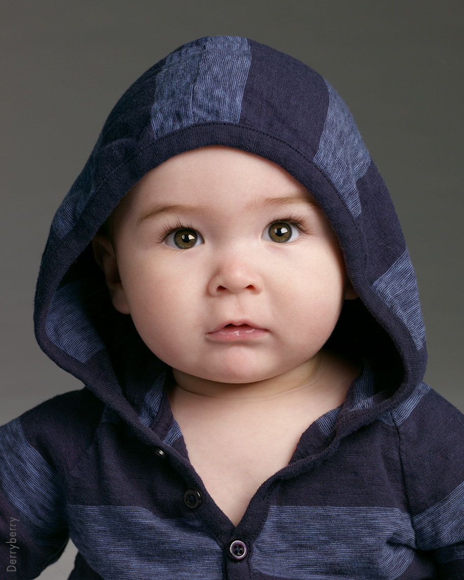 Portrait of a baby boy named Doc with a stripped blue hoody on.