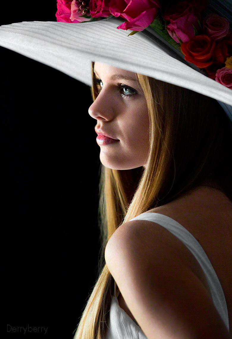 Color graduation day profile senior portrait  of Avery Hall  in flowered hat from Hockaday School in the studio  in Dallas, Texas by photographer John Derryberry Photography