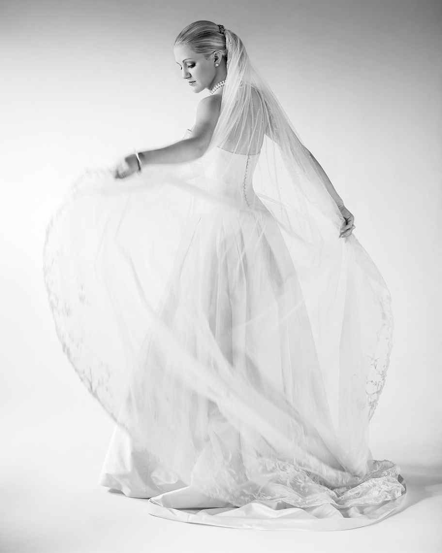 Black and white studio bridal portrait of bride spinning and holding her veil