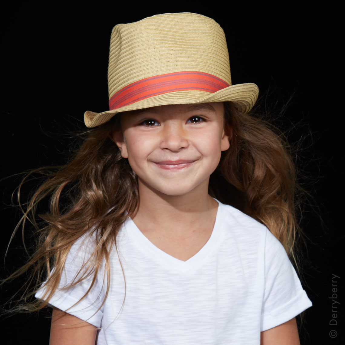Stylish color studio  portrait of a little girl in a straw hat and white t-shirt