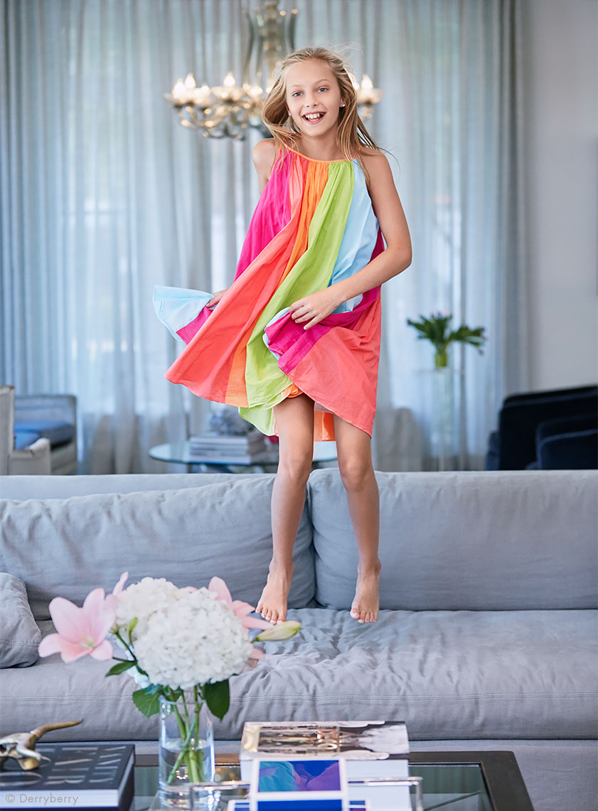 Fun color portrait of tween girl in a colorful dress jumping on a couch
