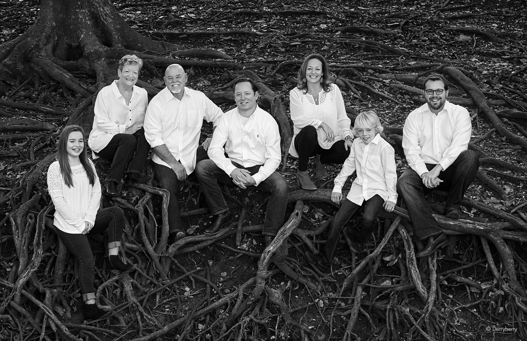 Black and white location group portrait of the Sowden extended family sitting in roots by a creek in Highland Park, Texas  by photographer John Derryberry Photography