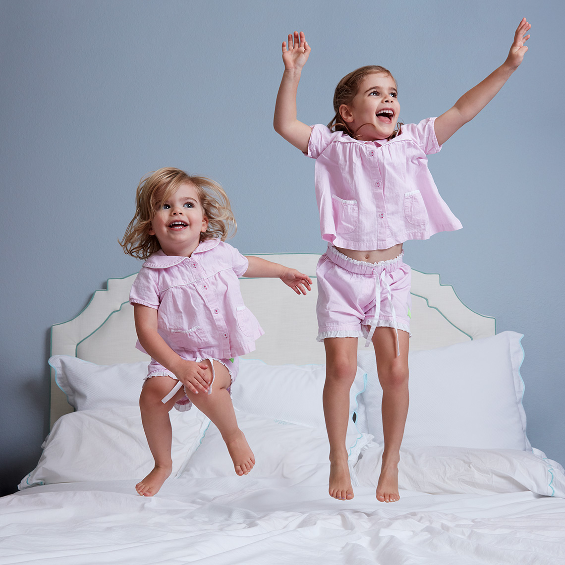 Color portrait of two little sisters in their pajamas jumping on their parent