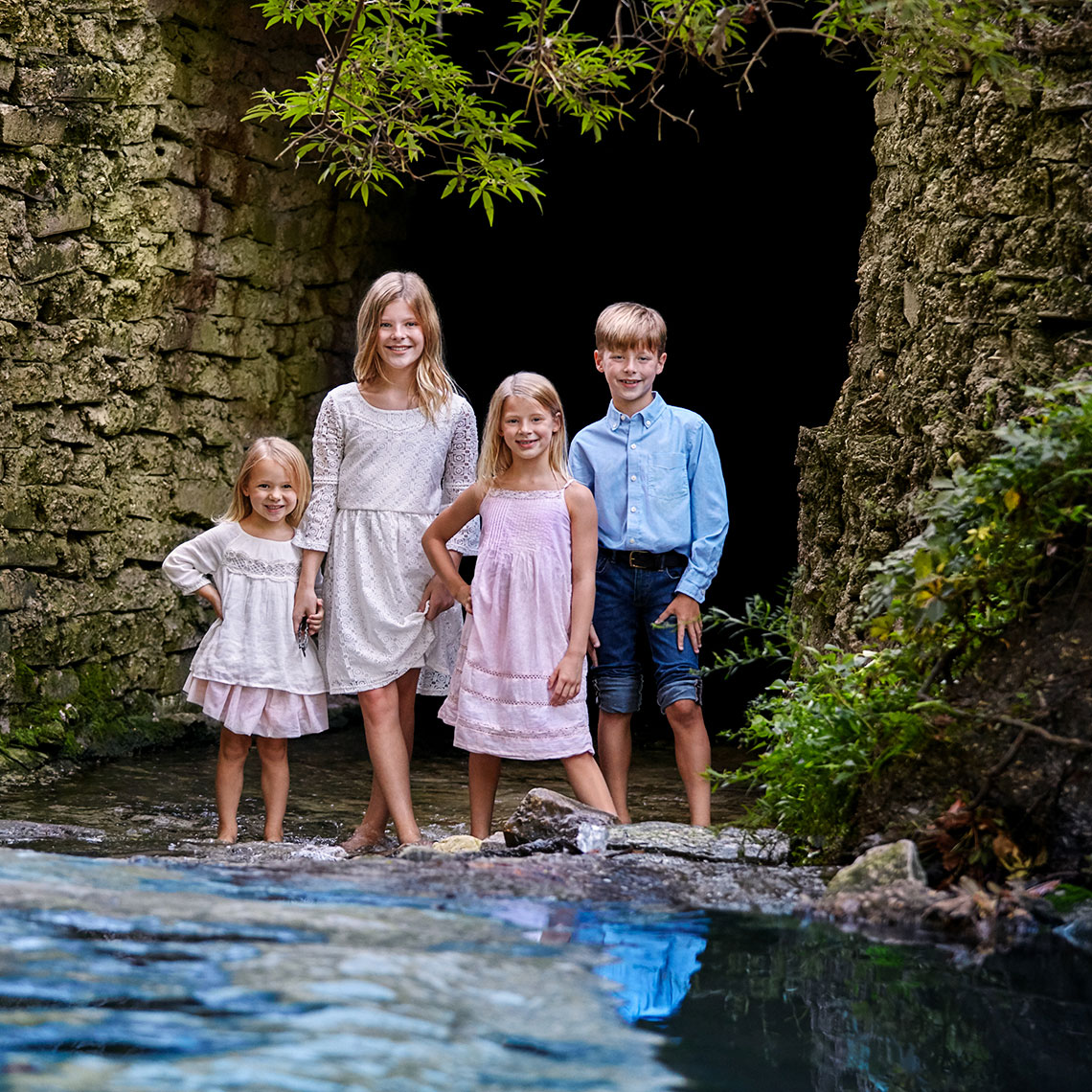 Color portrait of four, bare foot children in a creek by a cave by in Highland Park, Texas by John Derryberry