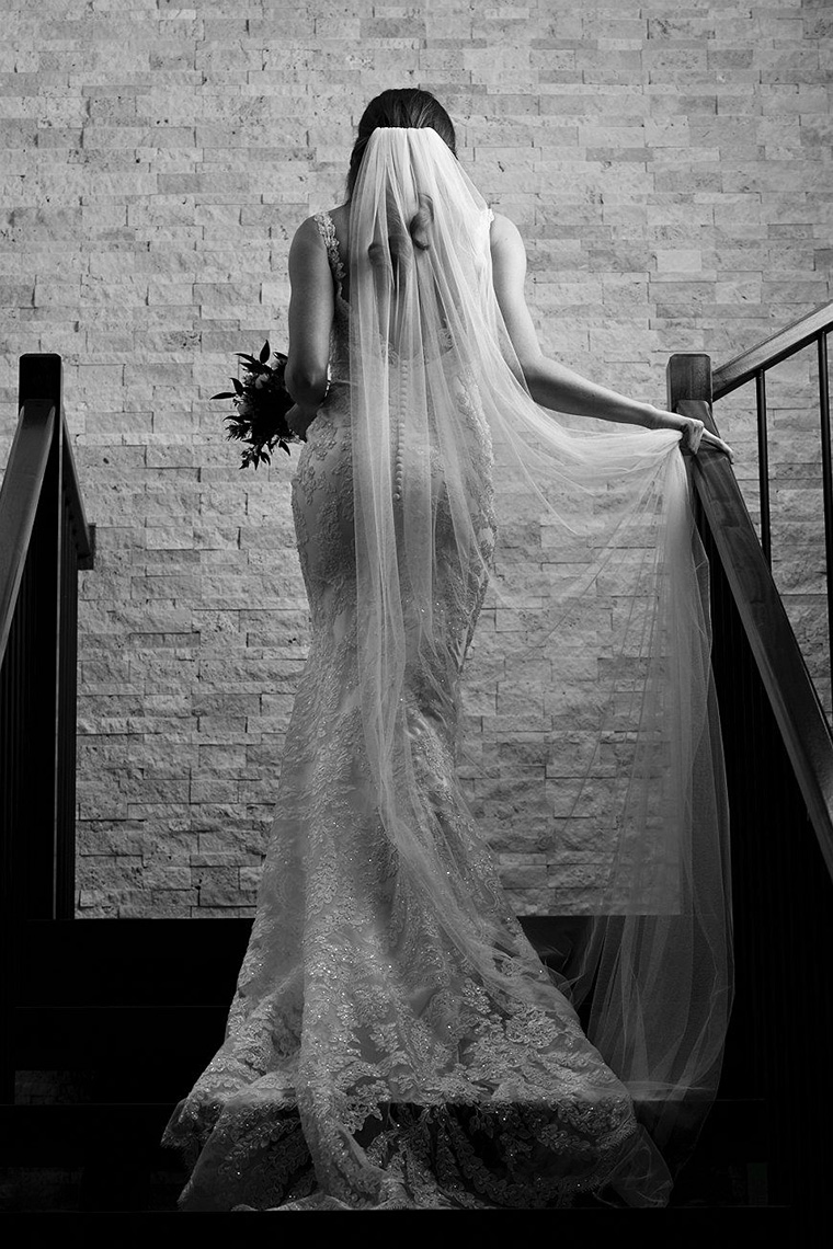 Black and white bridal portrait of a bride walking up stairs while holding her veil