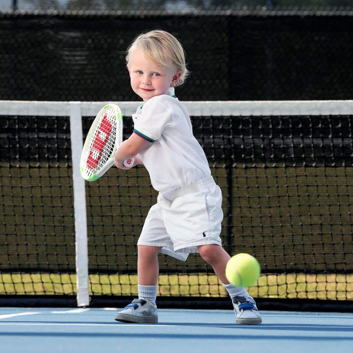 Color portrait of a blonde  little boy in white swinging a tennis racket to hit a ball