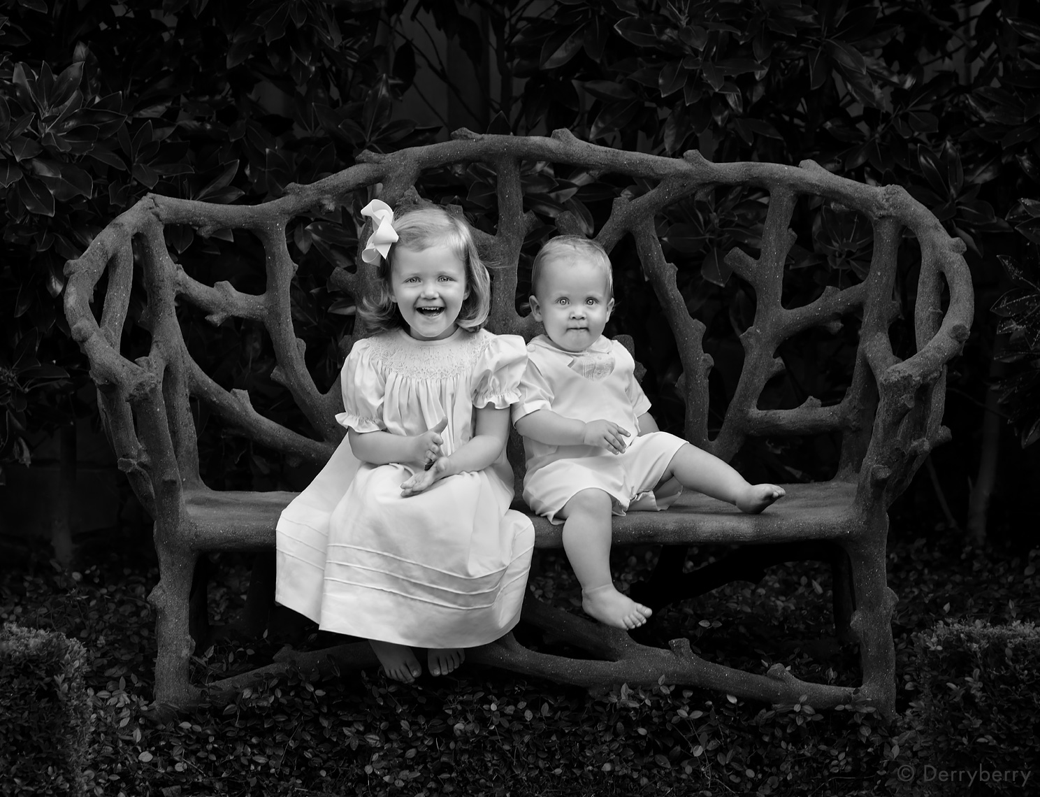 Black and white portrait of a young brother and sister sitting on a faux bois bench on location in a garden