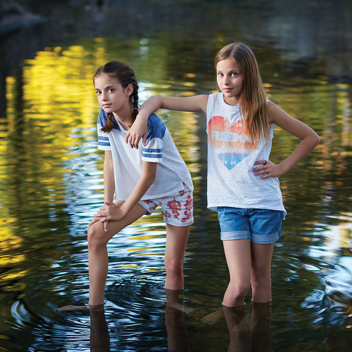 Color portrait of two sisters standing with an attitude in a creek in Highland Park by John Derryberry