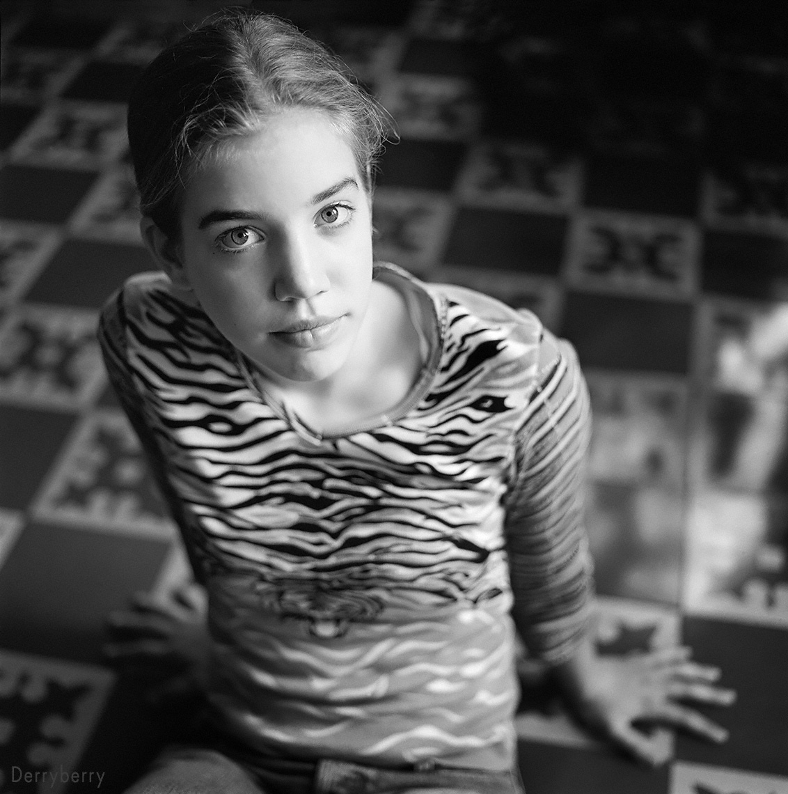 Portrait in black and white of tween girl in a tiger print shirt sitting on a beautiful vintage tile floor